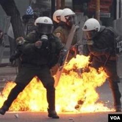 Polisi Yunani memadamkan bom-bom molotov yang dilemparkan oleh para demonstran.
