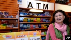 Owner Young Soolee basks in the attention at her small Alliance Center office bulding newsstand on Dec. 18, 2013, in Atlanta, after lottery officials said one of two winning Mega Millions lottery tickets were purchased from her store.