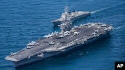 미군 항공모함 칼빈슨 호(왼쪽) 위로 미 해군 F/A-18 호넷, 슈퍼호넷 전투기들이 비행하고 있다. (자료사진)