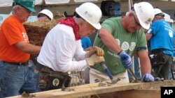 Mantan presiden AS Jimmy Carter (tengah), bekerja dalam proyek konstruksi lembaga Habitat for Humanity di Memphis, Tennessee (22/8). (AP/Adrian Sainz)