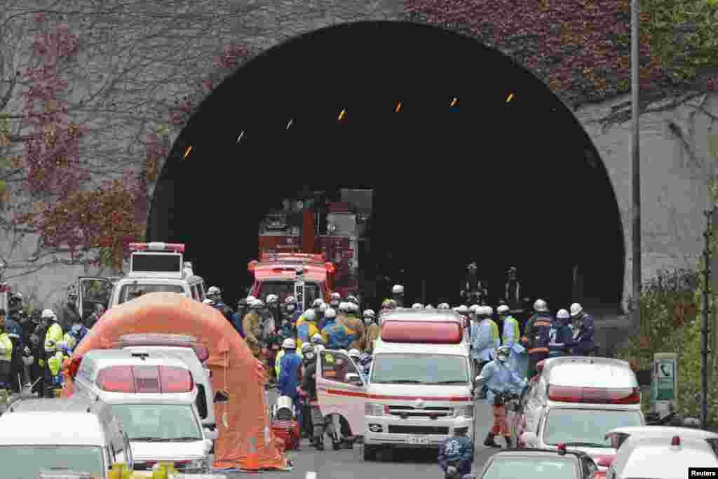 Cảnh sát và nhân viên cứu hỏa tụ tập trước cửa đường hầm Sasago. (Kyodo)