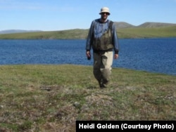 Study author Mark Urban walks back from field work in an Arctic lake where he is studying how climate change is affecting fish populations. (Credit: Heidi Golden)