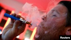 FILE - A customer puffs on an e-cigarette at the Henley Vaporium in New York City, Dec. 18, 2013.