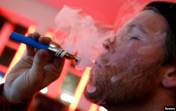 A customer puffs on an e-cigarette at the Henley Vaporium in New York City December 18, 2013. At the Henley Vaporium, one of a growing number of e-cigarette lounges sprouting up in New York and other U.S. cities, patrons can indulge in their choice of mor