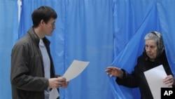 Một nữ cử tri vừa ra khỏi phòng bỏ phiếu ở Kiev, Ukraina, 28/10/12
