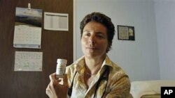 Dr. Lisa Sterman holds a bottle of Truvada pills that she prescribes for about a dozen patients at high risk for developing AIDS, at her office in San Francisco, May 20, 2012.