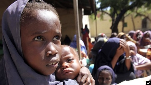 An internally displaced Somali girl carries her sibling as they wait to collect food relief from the World Food Program (WFP) in Mogadishu August 7, 2011.