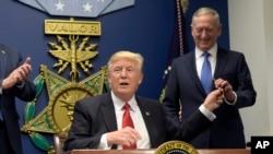 Prezidan Donald Trump (agoch) ap lonje yon plim bay Minis Defans lan, Jim Mattis, (adwat) apre li te fin siyen yon dekrè prezidansyèl sou ogmantasyon defans militè, nan Pentagon, tou pre Washington, 27 janvye 2017. (Foto: AP/Susan Walsh)