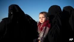 Seorang wanita menggendong seorang anak saat dia menunggu untuk diperiksa Pasukan Demokratik Suriah (SDF) yang didukung AS di gurun di luar Baghouz, Suriah, 1 Maret 2019. (Foto: AP)