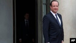 French President Francois Hollande waits on the front steps of the Elysee Palace in Paris prior to welcome his Polish counterpart Bronislaw Komorowski (not shown), May 7, 2013.