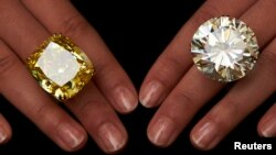 A model poses with a vivid yellow 100.09 carats diamond (L) and a 103.46 carats diamond ring during an auction preview at Sotheby's in Geneva May 7, 2014. These items are expected to reach between CHF 13,250,000 to 22,250,000 (USD 15,000,000 to 25,000,000