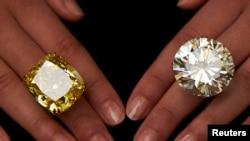Seorang model memamerkan cincin berlian warna kuning sebesar 100,09 karat (kiri) dan cincin berlian 103,46 karat dalam sebuah lelang di Sotheby's di Jenewa, 7 Mei 2014. (Foto: dok.)