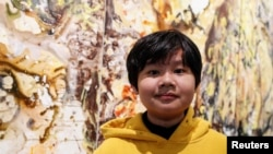 Xeo Chu, a young Vietnamese artist, stands in front of one of his pieces before his first solo show at the Georges Berges Gallery in New York City, New York, U.S., December 18, 2019. REUTERS/Shannon Stapleton
