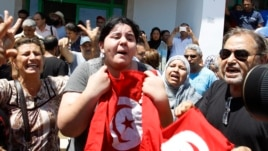 Assassinated Tunisian opposition politician Mohamed Brahmi's daughter Balkis (C) holds a Tunisian flag as she mourns his death in Tunis, July 25, 2013.