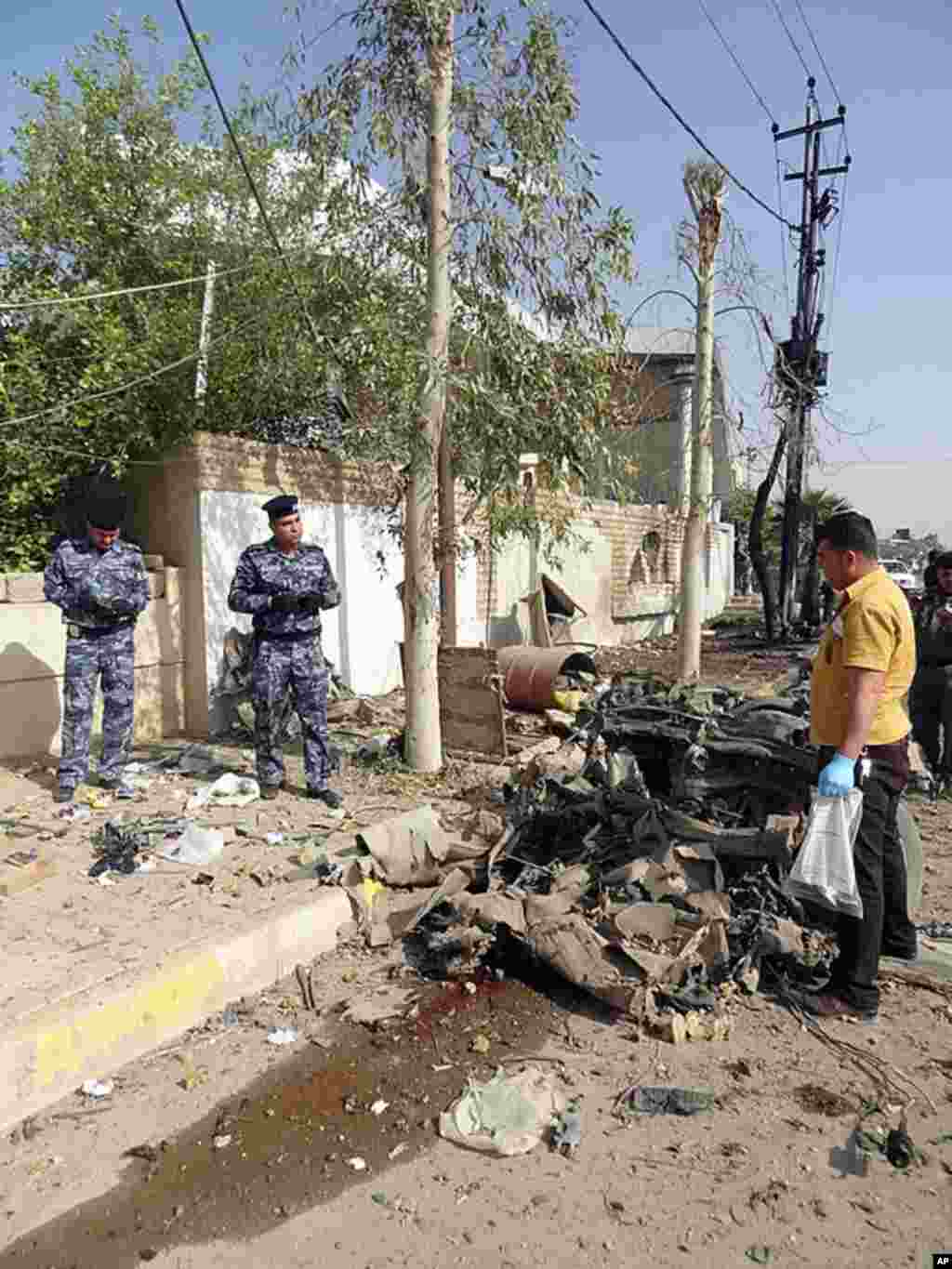 Iraqi inspect the remains of a vehicle at the scene of two car bombs in the northern oil-rich city of Kirkuk, which left several people dead, April 19, 2012. (AFP)