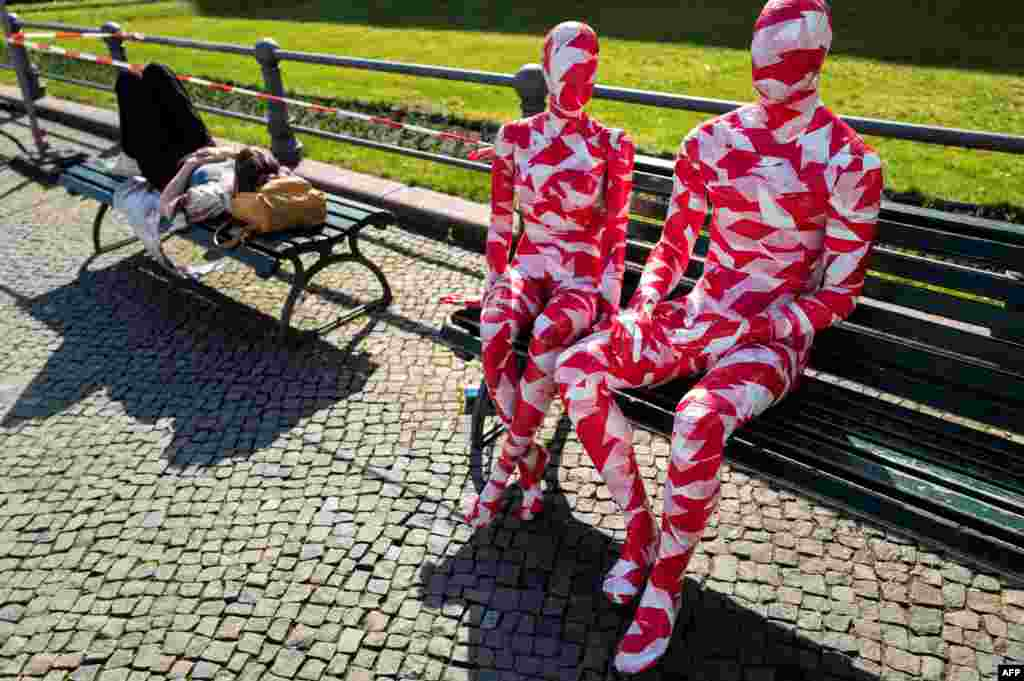 "A woman takes a nap on a bench next to mannequins wrapped in barrier tape near Berlin's landmark Brandenburg Gate as part of German artist Dennis Josef Meseg's Corona Memorial called ""It is Like it is."""