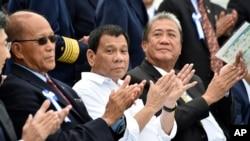 Philippine President Rodrigo Duterte, center, accompanied by Transportation Secretary Arthur Tugade, right, and Defense Secretary Delfin Lorenzana, left, clap their hands at the end of Japan's coast guard drills in Yokohama, Oct. 27, 2016.