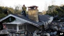 一名消防队员站在加州蒙地西托一处被泥石流掩盖的房屋顶上。(2018年1月10日)