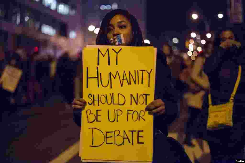 Seorang perempuan di Brooklyn, New York, memegang kertas yang menyerukan keadilan bagi Eric Garner(4/12)