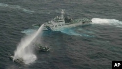 In this photo released by Japan Coast Guard 11th Regional Headquarters, a Japanese Coast Guard patrol boat uses water cannon to warn a Taiwanese leisure boat, left, and a Taiwanese Coast Guard boat off Uotsuri in Japanese and Diaoyu Dao in Chinese, January 24, 2013.