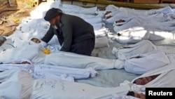 21일 시리아 다마스쿠스 외곽 고우타에서 정부군의 화학무기 공격으로 수백명이 사망했다는 주장이 나온 가운데, 한 남성이 사망한 아이의 시신을 살피고 있다.