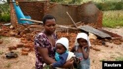 짐바브웨 치마니마니 지역에서 열대성 저기압 사이클론 '이다이'의 영향으로 집을 잃은 가족이 길 위에 서 있다.