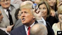 El republicano Donald Trump muestra un botón de campaña luego de hablar el domingo en Alabama.