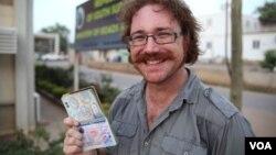 Graham Hughes memperlihatkan stempel visa terbaru dari Sudan Selatan di ibukota Juba. (Foto: VOA)