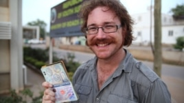 Graham Hughes brandishing his latest visa outside South Sudan's Ministry of Roads in Juba. The 33-year-old broke a world record when he reached South Sudan, the last on his list of 201 sovereign states to visit without flying.