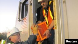 13일 미국 필라델피아의 열차 사고 현장에서 검사관이 운행기록장치를 꺼내고 있다.