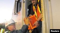 Penyelidik dari Dewan Keselamatan Transportasi Nasional AS (NTSB) membawa kotak hitam kereta yang keluar rel di Philadelphia, Pennsylvania (13/5).
