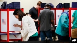 Voters fill out their ballots on the first day of early voting at the Hamilton County Board of Elections, Wednesday, Oct. 10, 2018, in Cincinnati. In-person voting has begun in swing-state Ohio for the Nov. 6 elections for governor, U.S. Senate, House seats and a host of other state and local offices and issues. Registration closed Tuesday, and county voting centers opened Wednesday morning. (AP Photo/John Minchillo)