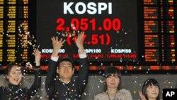 ພະນັກງານຕະຫລາດຫຸ້ນທີ່ເກົາຫລີໃຕ້ ສະແດງຄວາມດີໃຈ ທີ່ຕະຫລາດຫຸ້ນຂອງປະເທດ ປະສົບຜົນສໍາເລັດ ຍ້ອນຫຸ້ນຂຶ້ນລາຄາຢ່າງຫລວງຫລາຍ ໃນປີ 2010. REUTERS/Jo Yong-Hak (SOUTH KOREA - Tags: BUSINESS)