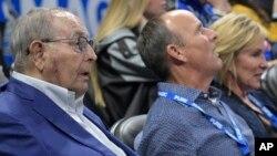 FILE - Orlando Magic owner Rich DeVos (L), his son, Amway president Doug DeVos (C), and daughter-in-law, Maria DeVos, watch from their court side seats during the first half of an NBA basketball game against the Houston Rockets Jan. 3, 2018, in Orlando, FLA.