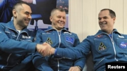 International Space Station (ISS) crew members Russian cosmonauts Evgeny Tarelkin (L) and Oleg Novitskiy (C) and U.S. astronaut Kevin Ford sit together at Kustanay Airport after they landed near the town of Arkalyk, March 16, 2013.