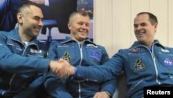 国际空间站的俄罗斯宇航员奥列格.诺维茨基(中)和叶夫根尼.塔列尔金(左)和美国宇航员凯文.福特2013年3月16日在阿尔卡雷克镇附近安全着陆后,在库斯塔奈机场坐在一块