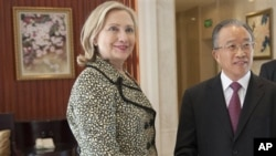 Chinese State Councilor Dai Bingguo, right, and U.S. Secretary of State Hillary Rodham Clinton shake hands prior to their meetings at Kylin Villa in Shenzhen, China, Monday, July 25, 2011. (AP Photo/Saul Loeb, Pool)