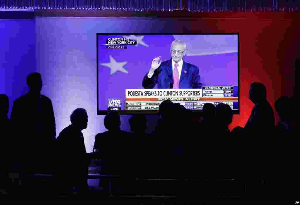 Les partisans de Donald Trump regardent John Podesta, le directeur de campagne de la candidate démocrate à la présidentielle, Hillary Clinton, parler à New York, le 9 novembre 2016.