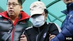 Penjaga Pantai Korea Selatan menggiring kapten kapal nelayan Tiongkok (tengah) pasca perawatan medis di rumah sakit Incheon (12/12).