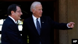 US Vice President Joe Biden (R) points as Cypriot President Nicos Anastasiades smiles before their meeting in the Cypriot capital Nicosia on May 22, 2014.