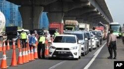 Para petugas kepolisian mengecek mobil-mobil di jalan tol Cikarang, Jawa Barat, untuk mencegah warga agar tidak pulang kampung di tengah pandemi virus corona, 24 April 2020.
