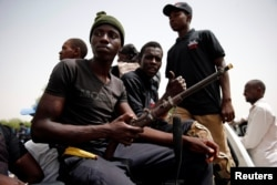 FILE - Members of a local militia, otherwise known as CJTF, sit in the back of a truck during a patrol in the city of Maiduguri, northern Nigeria, June 9, 2017.