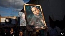 Những đứa trẻ mang theo những bức ảnh của Fidel Castro và Che Guevara trong một đoàn diễu hành tại Regla, Cuba, 08 tháng 1, 2015.