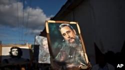 Timoun kap pote ankadreman ki gen imaj Fidel Castro ak Che Guevara pandan yon selebrasyon nan lari pou komemore 56èm anivèsè rejim kominis la nan peyi ak tryonf chèf lame rebèl la Castro, nan Regla, Kiba, 8 janvye , 2015.