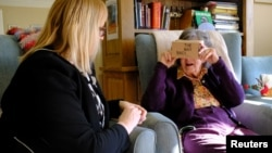 FILE - Daphne Padfield, 93, tries out a specialist virtual reality headset at the Langham Court Dementia Home in Hindhead, Britain, Feb. 6, 2018.