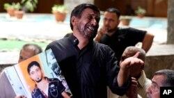 Một người cha đau khổ mang bức ảnh của con trai ông, một người lính Iraq, đến phòng xử án tại Baghdad. (AP/ Karim Kadim).