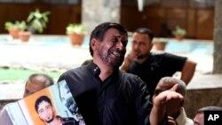 2014年7月8日伊拉克巴格达法庭悲伤的父亲展示死去的儿子照片