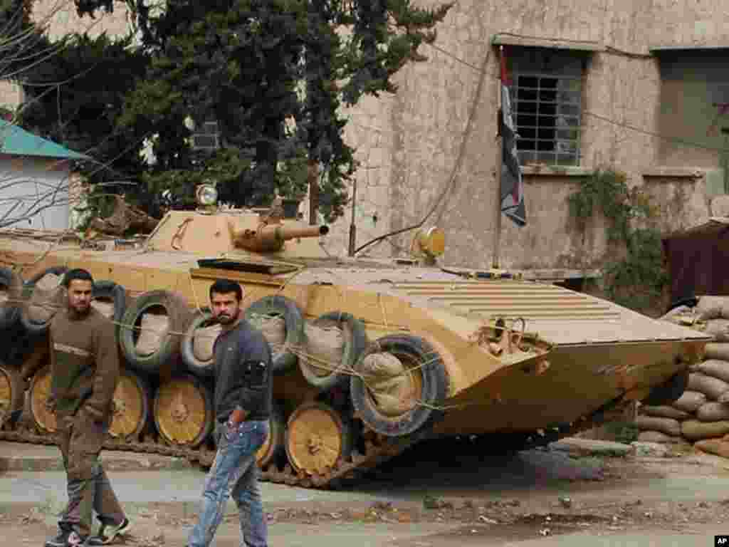 Syrian government-organized media tour, February 15, 2012, shows an armored personnel carrier in the Damascus suburb Harasta that saw heavy fighting earlier this year. (AP)