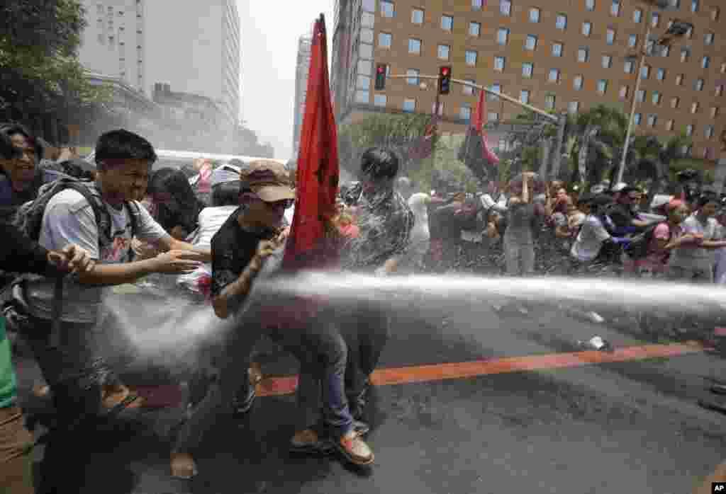 필리핀 마닐라 미 대사관 앞에서 바락 오바마 대통령의 방문에 항의하는 반미 시위대에 경찰이 물대포를 쏘고 있다.