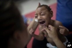One-year-old Jose Wesley Campos, who was born with microcephaly, cries during a physical treatment at the AACD rehabilitation center in Recife, Brazil, Sept. 28, 2016.